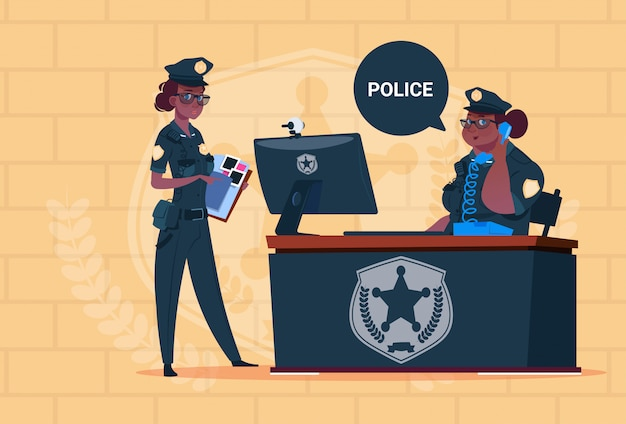 Twee afrikaanse amerikaanse politievrouwen die aan computer werken die eenvormige vrouwelijke wachten op blauwe bakstenenachtergrond dragen Premium Vector