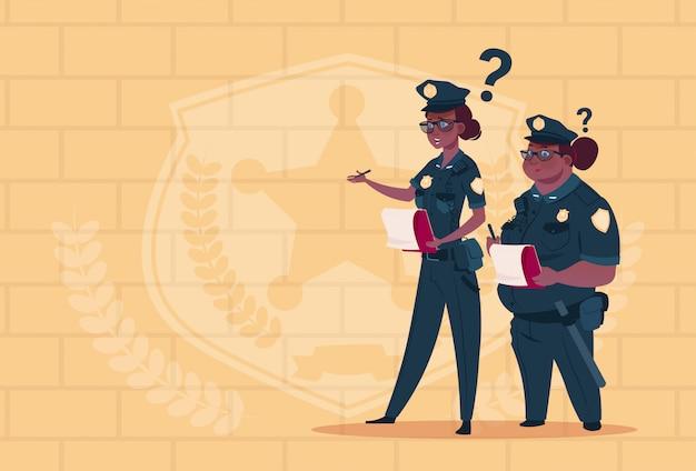 Twee afro-amerikaanse politie-vrouwen houden vakken met office-personeel ontslagen dragen uniforme bewakers op blauwe bakstenen achtergrond Premium Vector