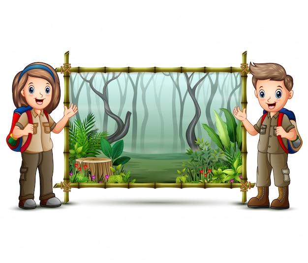 Verkennerjongen en meisje dichtbij het groene bamboekader Premium Vector