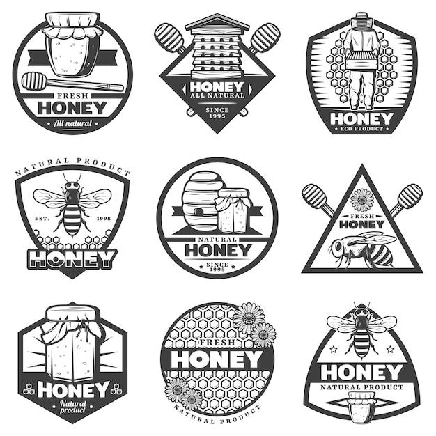 Vintage monochrome honingetiketten instellen met bijenkorf imker stokken bijen bloemen potten honingraten geïsoleerd Gratis Vector