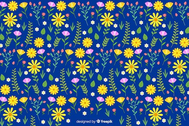 Vlakke kleurrijke bloemen en bladerenachtergrond Gratis Vector
