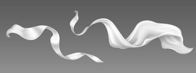 Vliegende witte zijden lint en satijnen stof. realistische set golvende fluwelen kleding, sjaal of cape in de wind. luxe wit textiel draperie, stromend weefsel geïsoleerd op een grijze achtergrond Gratis Vector