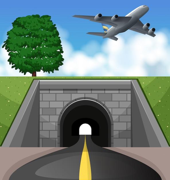 Vliegtuig die over de tunnel vliegen Premium Vector