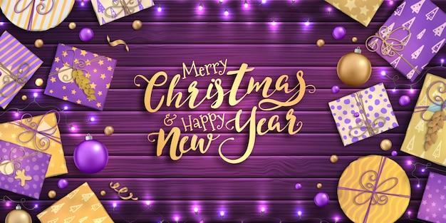 Vrolijk kerstfeest en een gelukkig nieuwjaar. achtergrond met kerstdecoratie - paarse en gouden kerstballen, ambachtelijke geschenkdozen en slingers op houten achtergrond Premium Vector