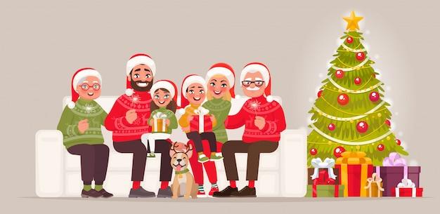 Vrolijk kerstfeest en een gelukkig nieuwjaar. grote familie zittend op de bank naast de kerstboom met geschenken Premium Vector