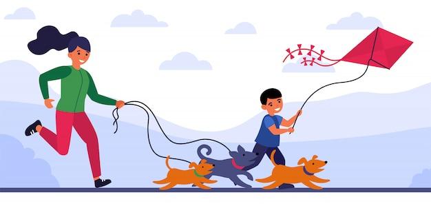 Vrouw die achter honden loopt, en haar zoon na vlieger Gratis Vector