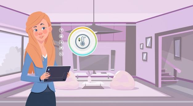 Vrouw die digitale tablet houdt die slim huisapp over woonkamer achtergrond moderne technologie van het concept van de huiscontrole gebruikt Premium Vector