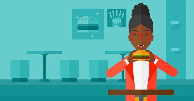 Vrouw die hamburger eet. Premium Vector