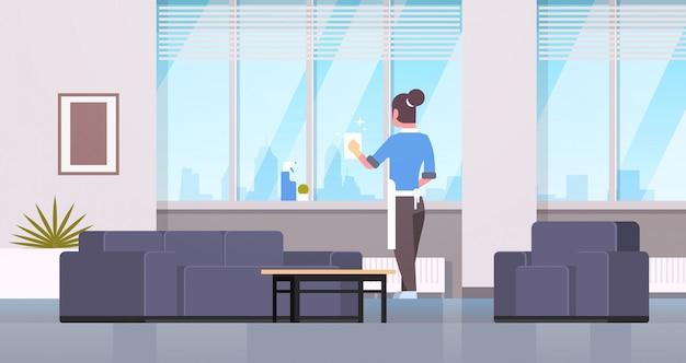 Vrouw in handschoenen en schort ramen met vod schonere spray achteraanzicht huisvrouw huishoudelijk werk concept moderne woonkamer interieur schoonmaken Premium Vector