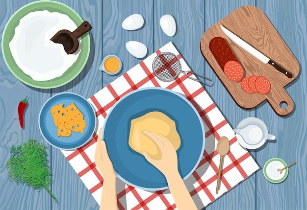 Vrouw kneedt het deeg op een blauwe tafel. uitzicht van boven. pizza koken. ingrediënten op tafel. illustrtion Premium Vector