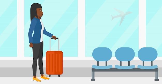 Vrouw op luchthaven met koffer Premium Vector