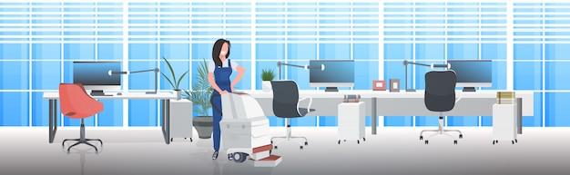 Vrouwelijke conciërge met behulp van stofzuiger lachende vrouw in uniforme vloer zorg schoonmaak concept moderne kantoor interieur horizontale volledige lengte Premium Vector