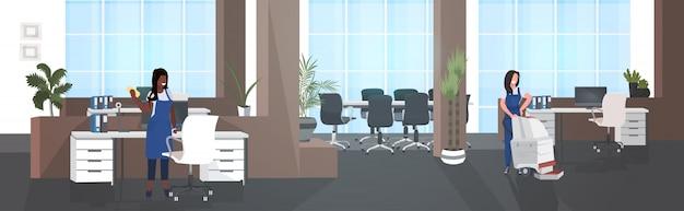Vrouwelijke schoonmakers met behulp van stofzuiger en vod mix race conciërges team in uniform samen te werken schoonmaak concept moderne kantoor interieur horizontale volledige lengte Premium Vector