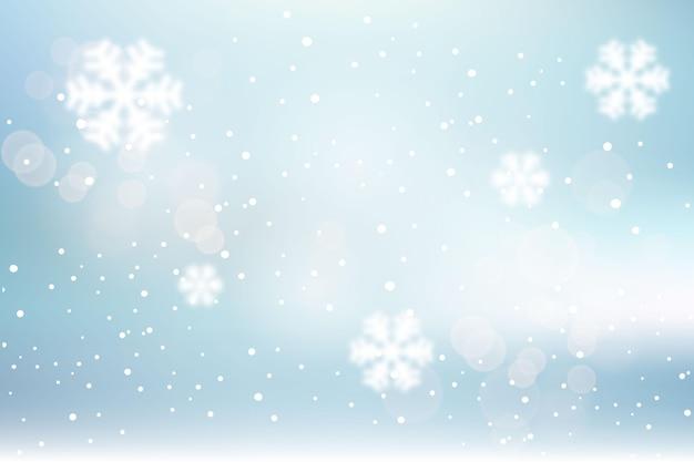 Wazig winter achtergrond met sneeuwvlokken Gratis Vector