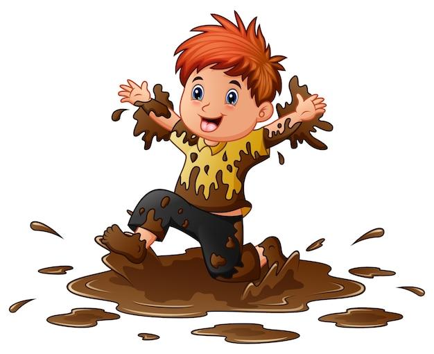 Weinig jongen die in de modder speelt Premium Vector