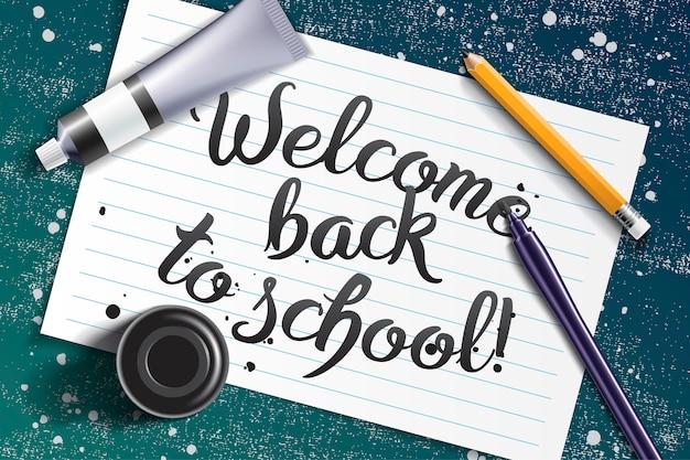 Welkom terug op school handgetekende letters met kalligrafie mockup met penseel pen, scherp potlood, verf tube en zwarte inktfles op de ruimte van wit vel papier en grunge krijtbord Premium Vector