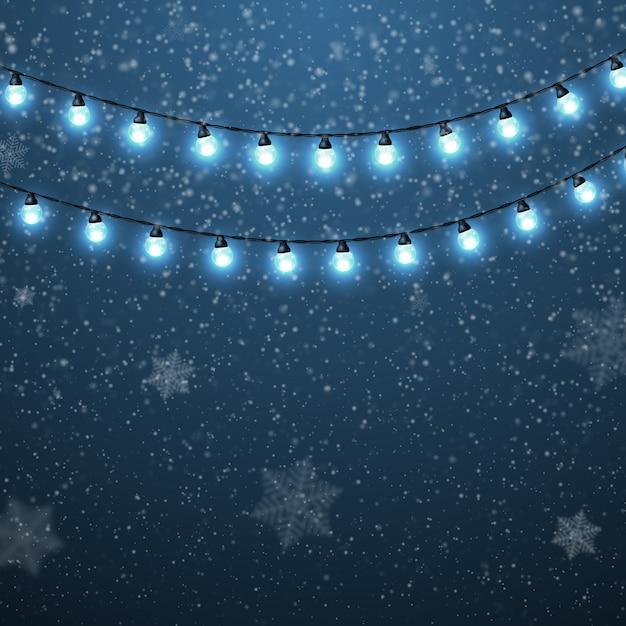 Winterlandschap met vallende sneeuw van kerstmis en heldere lichtgevende slingers. Premium Vector