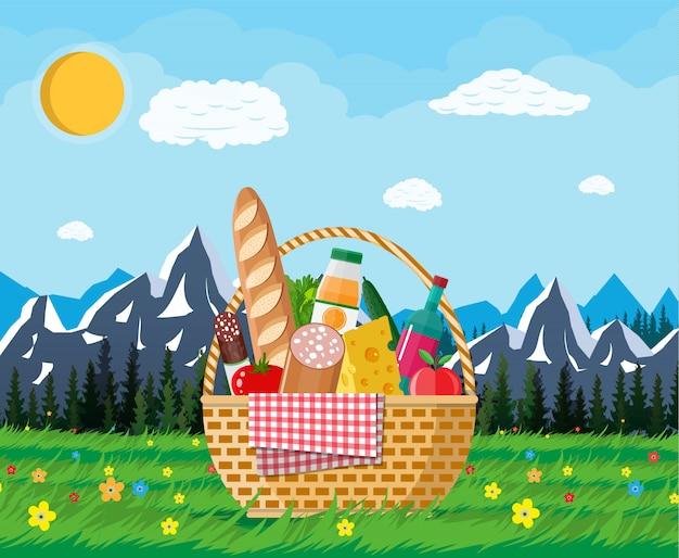 Witte picknickmand vol producten en natuur Premium Vector