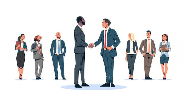 Zakenlieden handdruk overeenkomst concept mix race zakenmannen teamleider handbewegingen internationale samenwerking communicatie stripfiguur geïsoleerd plat volledige lengte horizontaal Premium Vector
