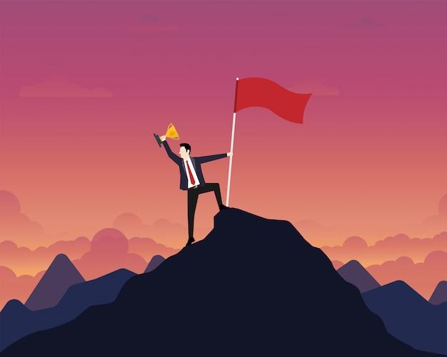 Zakenman die een gouden trofeekop met succesvlag steunen bovenop berg Premium Vector