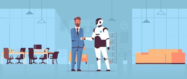 Zakenman en robot handshaking tijdens het voldoen aan overeenkomst partnerschap kunstmatige intelligentie futuristische mechanisme technologie modern kantoor interieur Premium Vector