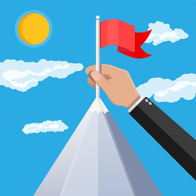 Zakenman hand zet vlag op de top van de berg. Premium Vector