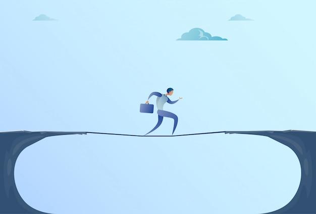 Zakenman walk over cliff gap mountain business man balancing houten stokbrug Premium Vector
