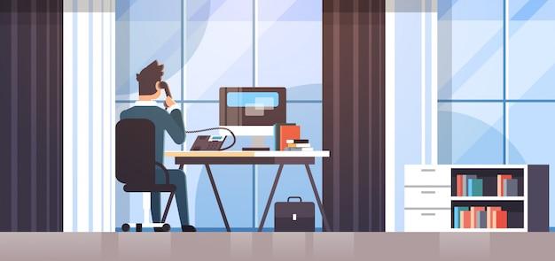 Zakenman zittend op werkplek bureau achteraanzicht zakenman met behulp van computer tijdens het praten over vaste telefoon werkproces creatieve kantoor interieur Premium Vector