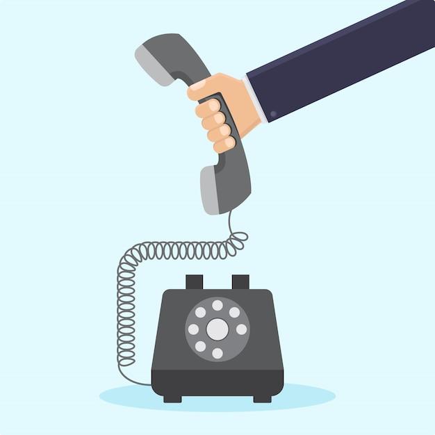 Zakenmanhand die retro telefoon vlakke illustratie houden Premium Vector