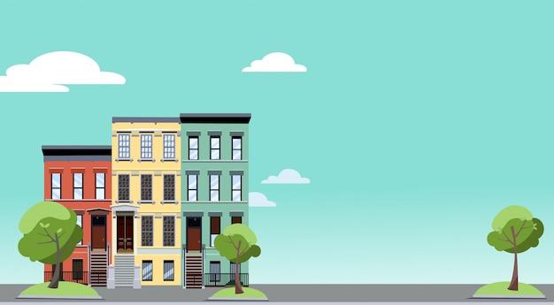 Zomer in de stad. kleurrijke stadsgezicht met gezellige groene bomen in de buurt van huizen met twee verdiepingen. Premium Vector