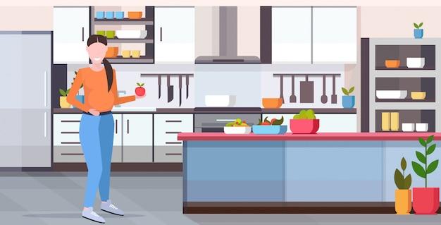 Zwanger de appelmeisje die van de vrouwenholding verse vruchten en groenten eten het concept van het zwangerschapsmoederschap moderne keuken binnenlandse volledige horizontale lengte Premium Vector